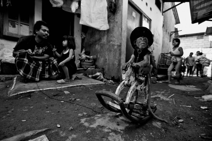 A monkey practices riding a wooden horse at Kampung Cipinang Besar in Jakarta.  Photo by Ed Wray