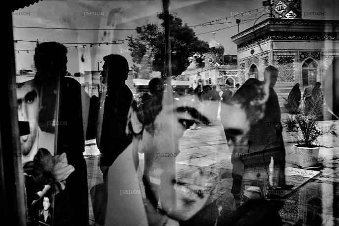 The faces of 'martyrs' killed during the Iran-Iraq war (1980-88) are reflected as a funeral takes place in the cemetery in the main square in Qom. Photo by Espen Rasmussen