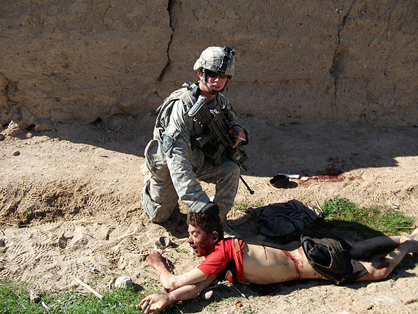 "This image, published by Rolling Stone, shows the body of Gul Mudin, the son of a farmer, who was killed on Jan. 15, 2010. Pfc. Andrew Holmes, a member of the ""kill team"" is posing next to him."