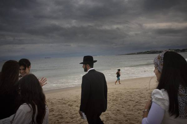 Copacabana beach. The sea sometimes also attracts the followers of some of the various religions present in the country. In this case, a group of Jewish faithfuls are praying during the day of Yom Kippur.Rio de Janeiro, Brazil. September 2009. Photo by Francesco Zizola