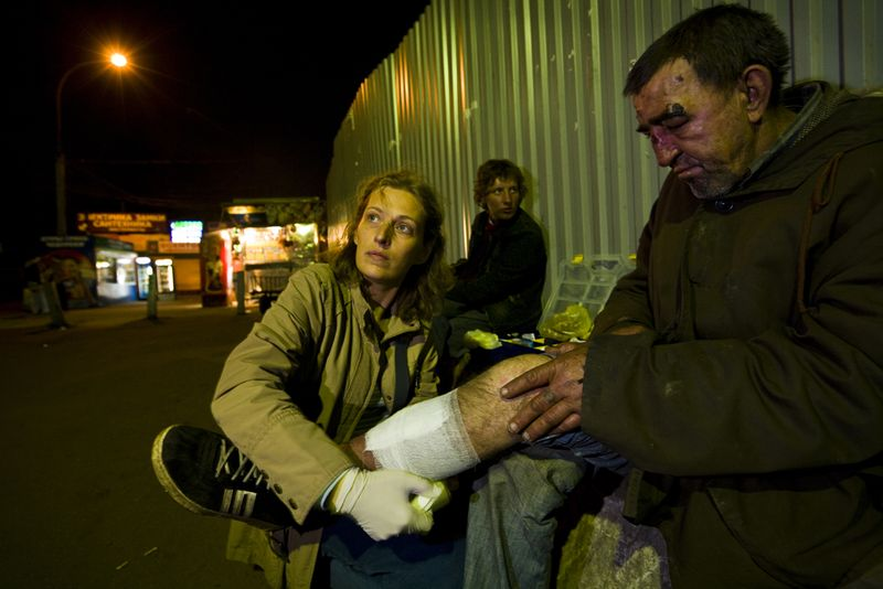Like an angel of the night, volunteer Tatyana Sveshnikova, 35 and a teacher by training, working in cooperation with the Russian Orthodox Church, attends to a battered homeless man near Kursk Station with aid collected from personal friends and family. Photo by Gerd Ludwig