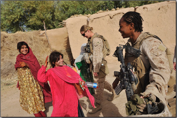 United States Marine Cpl. Christina Oliver, 25, right, laughs with a local girl during a patrol with a female engagement team or FET. Though the overall mission of the FET teams is to engage Afghan women, the female Marines are increasingly exposed to small arms fire and improvised explosive attacks. Photo by Lynsey Addario