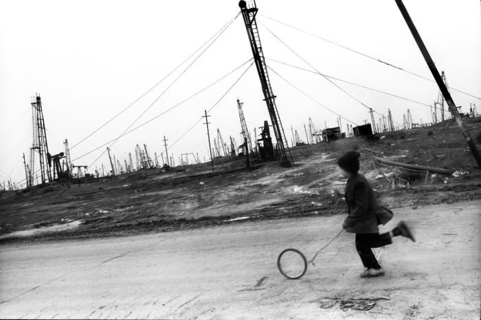 Boy running with a self-made toy. Balakhani oil village. Azerbaijan. 2004. Photo by Rena Effendi