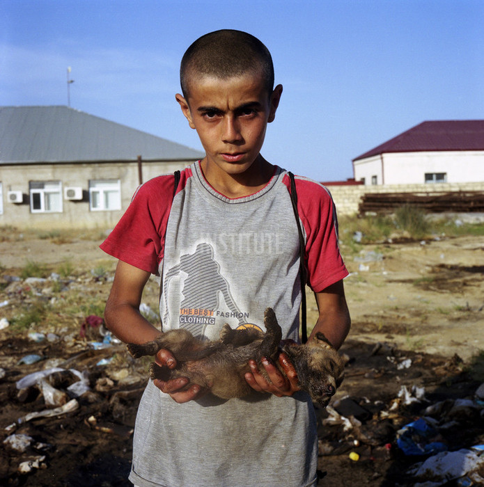 Boy holding a puppy smudged in oil. Balakhani village. Baku, Azerbaijan. 2010. Photo by Rena Effendi