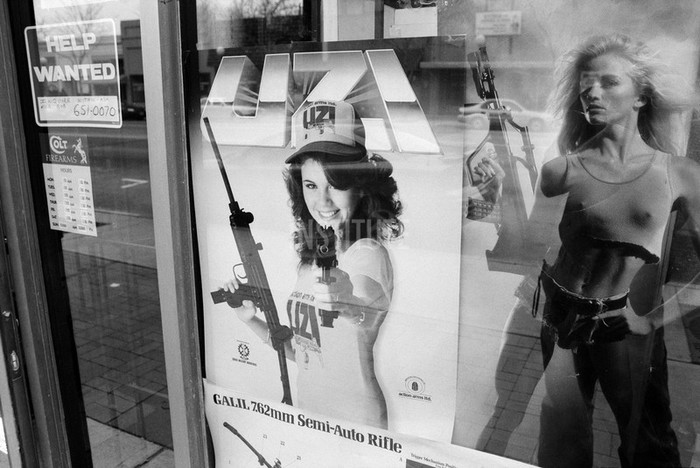 Posters advertising military-designed assault weapons, in the window of Paladin Arms, a gun-store in Longmont, Colorado. Semi-automatic assault rifles may be legally purchased over-the-counter by anyone over the age of 18 in the state of Colorado. Photo by Zed Nelson