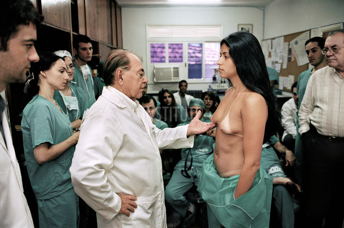 "Dr. Pitanguy with prospective patient, watched by his team of trainee plastic surgeons. Dr. Pitanguy is known in Brazil as ""The Pope of Plastic Surgery"", and one of the nation?s most successful plastic surgeons. Once a month he offers free cosmetic surgery to Brazil?s poor. Many come from the nation's favella's seeking breast implants, nose-jobs and tummy-tucks. Those selected are operated on either by himself or one of his large team of trainee plastic surgeons. Rio, Brazil. Photo by Zed Nelson"