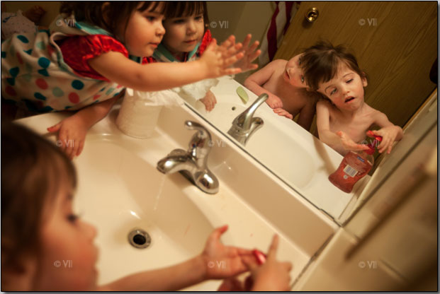 Sister Shaylee Hogan keeps Tatiana and Krista Hogan company as they wash their hands. Photo by Stephanie Sinclair