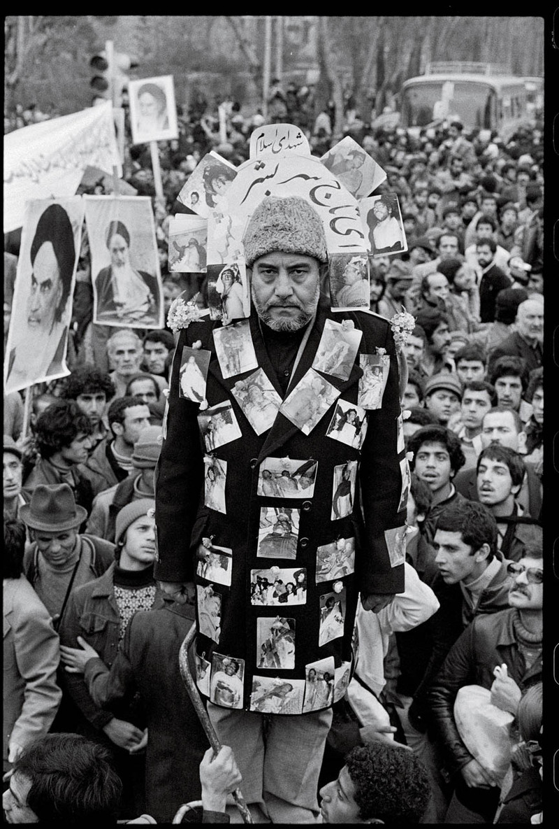 "A pro-Khomeini demonstrator dons a jacket decorated with photographs of victims of the Shah's repression and a hat that reads ""crown of the martyrs."" Tehran, Jan. 19, 1979. Photo by David Burnett"