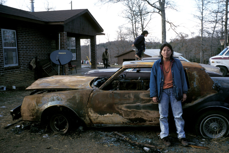 Joyce Wildcat stands in front of her burned out car in the yard of her family home in Big Hollow, Okla. She is a traditional full-blooded Cherokee-Creek and is the black sheep of the Wildcat family, always getting into trouble. Photo by Maggie Steber