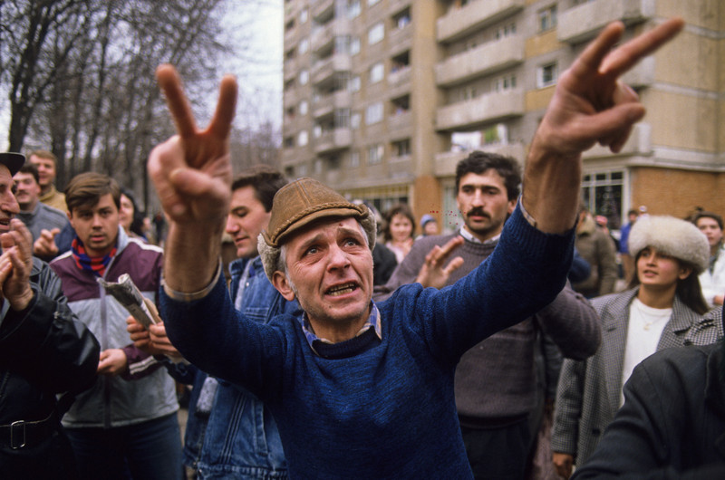 "Romanians in Bucharest celebrated the overthrow of the regime of Nicolae Ceausescu during the Romanian Revolution, December 1989. This man, beside himself with fury and relief, jabbed twin victory signs at an unseen target and repeatedly shouted, ""Ceausescu Dictator."" Photo by Peter Turnley / Cprbis"