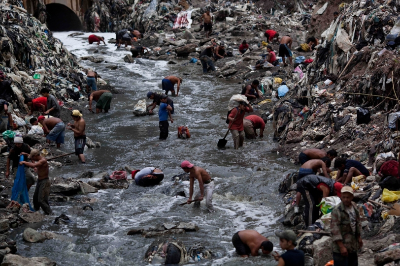 "Informal workers search for scrap metal in contaminated water at the bottom of one of the biggest trash dumps in the city, known as ""The Mine,"" in Guatemala City. Photo by Rodrigo Abd"
