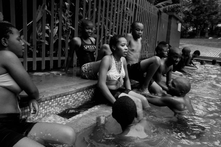 "Young men flirt with teenage girls at a local swimming pool. From the project ""HIV In Swazi"" - Photo by  Krisanne Johnson"