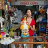 Lennna Pupo, 21, sells religious objects for the Cuban Santeria rituals. Dolls, costumes, prayer books and more mysterious objects are between the offerings. She does not sell animals for the sacrifices, a different license is needed for that. The shop is in the most touristic street in Havana, Calle Obispo, but the clients are almost exclusively Cuban. Havana, Cuba. 2012 - Photo by Paolo Woods