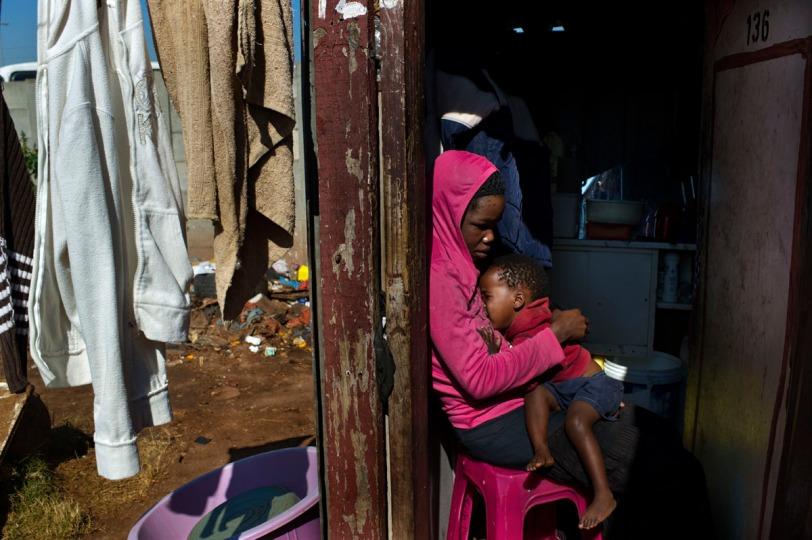 A young woman and her son washing clothes  in a city outskirt slum. These slum buildings are overcrowded, warren-like spaces, which lack proper waste and sewage management, often have unsanitary or inaccessible water, and little or no electricity.  June 2011. Photo by Pep Bonet