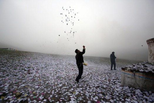 "A man throws small pieces of paper, called ""wind horses,"" into the air. The practice is said to bring good luck. Photo by Sean Gallagher"