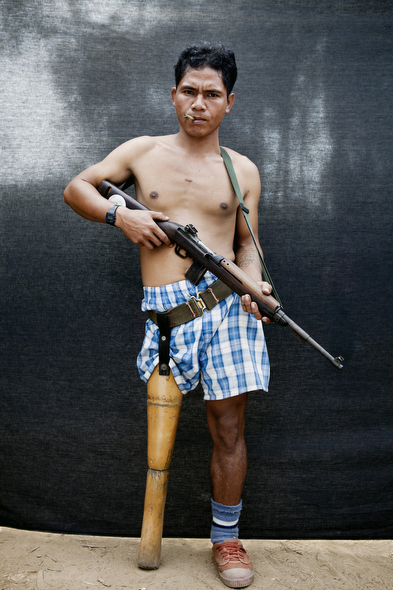 Kyaw Mya, a KNLA medic who lost his leg in a landmine explosion, poses with a gun. Photo by Jason Florio