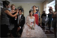 Farid Aliyev, 23, and Khanim Veliyeva, 20, pose for pictures in his home on the third day of a traditional three day wedding in Givrakh, Nakhchivan Autonomous Region, Azerbaijan. Once the bride is delivered to the groom's family's house, she will stay with the family and live the rest of her life in her new home. Photo by Amanda Rivkin