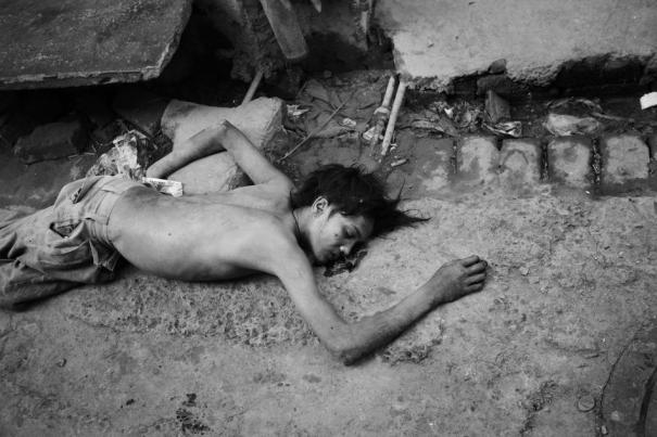 A 17 year old boy lies dead in a dirty alley. A few hours before, he was beaten to death over an argument about drugs and money. Photo by Enrico Fabian