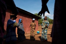 Female members of a village committee in South Kivu dance around a women's center. Photo by Lynsey Addario