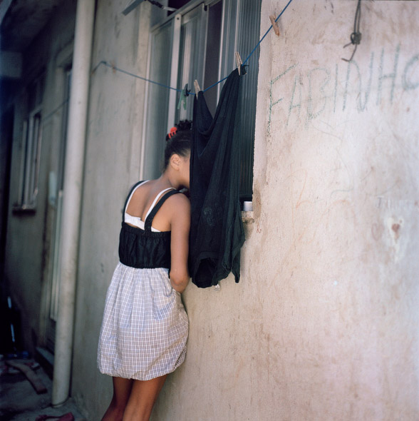 A young resident looks inside her family's home in Largo do Tanque, a favela in Rio de Jainero. Photo by Lianne Milton