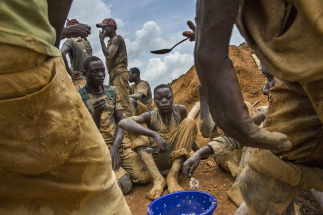 Miners eat lunch from a communal bowl in the mining town of Pluto. Photo by Marcus Bleasdale